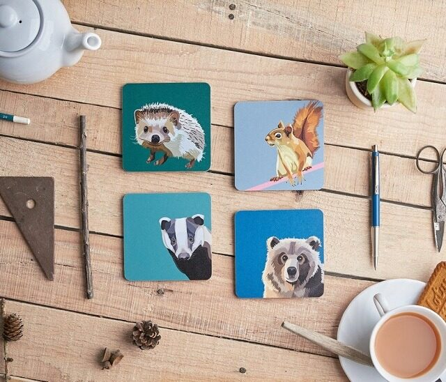 woodland animal coasters featuring bear badger hedgehog squirrel against wooden table with cup