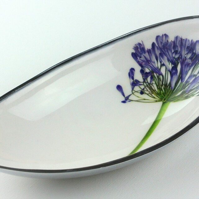 boat shaped white ceramic bowl decorated with a blue agapanthus flower