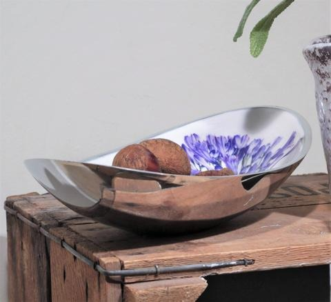 boat shaped bowl decorated with hand painted blue agapanthus flowers with nuts in it, resting on an upturned crate
