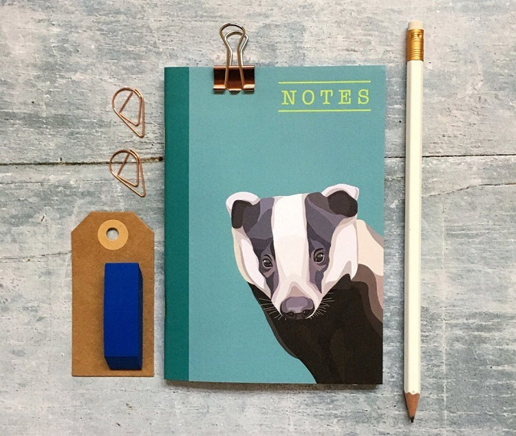 badger notebook by arch and ivy against a grey background with a pencil and luggage tag