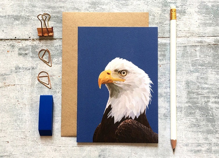 bald eagle card against grey background with pencil eraser and paper clips