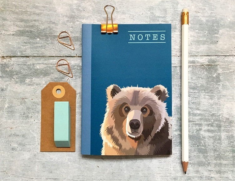 bear notebook against a grey background with pencil and luggage tag