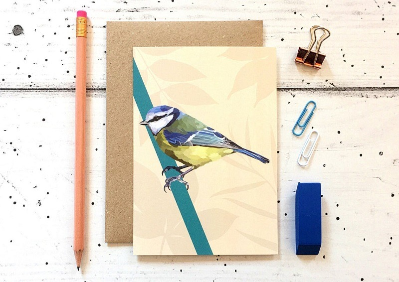 blue tit card against cream background with pencil eraser and paper clips
