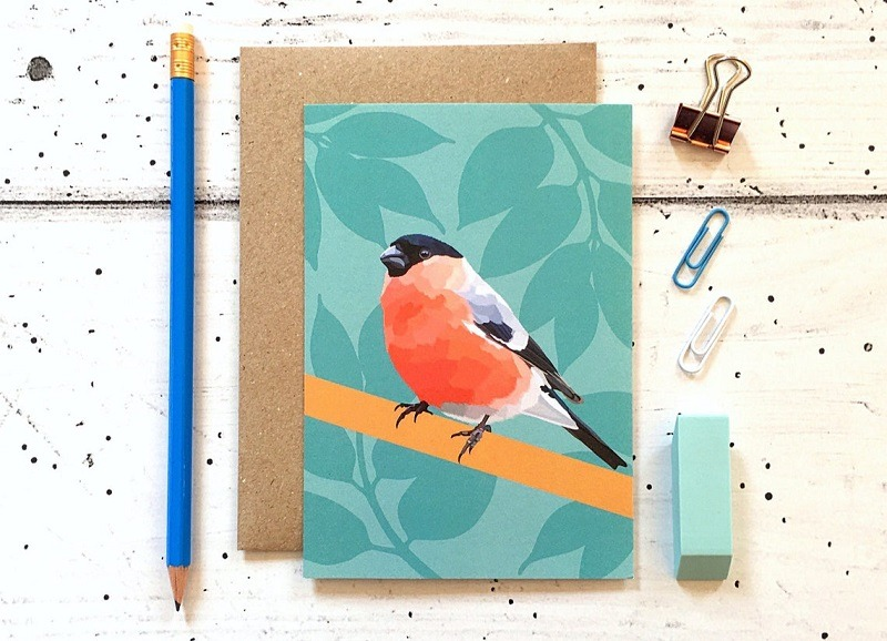 bullfinch card against cream background with pencil eraser and paper clips