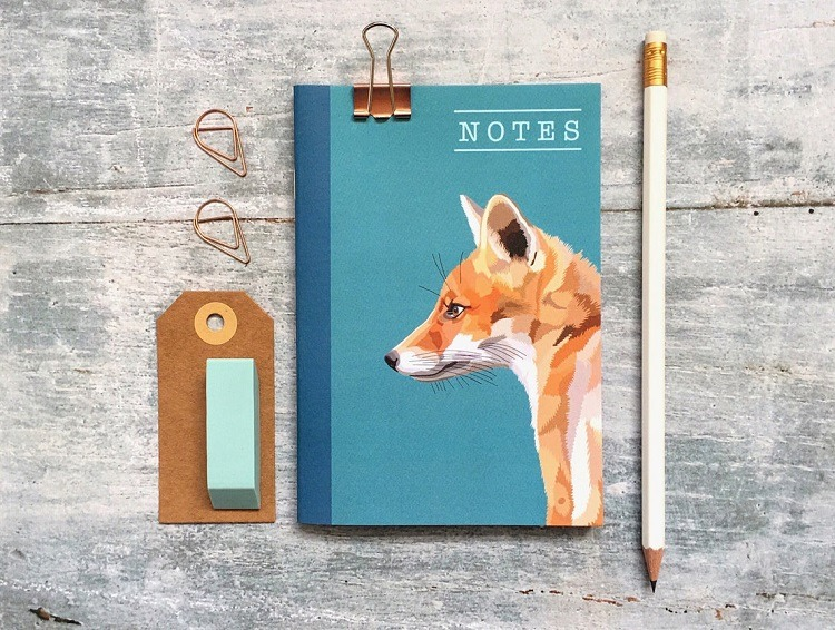 fox notebook against a grey background with pencil and luggage tag