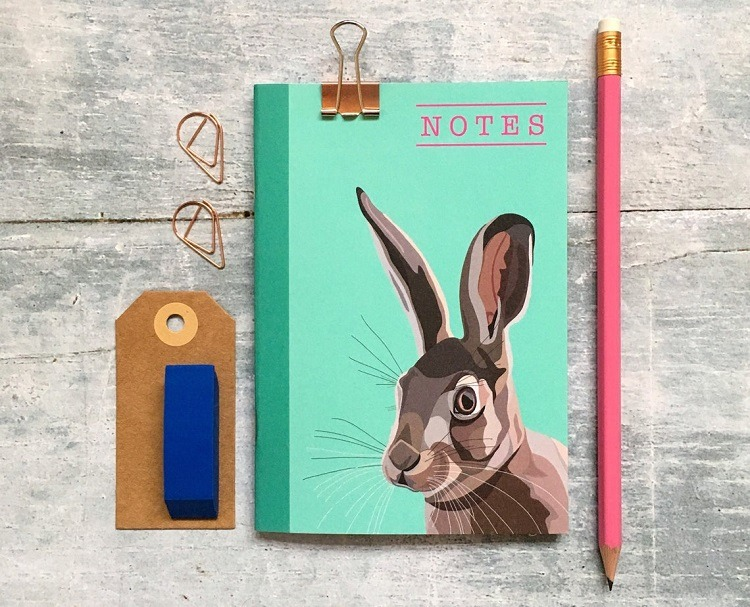 Hare notebook by arch and ivy against a grey background with pencil and luggage tag
