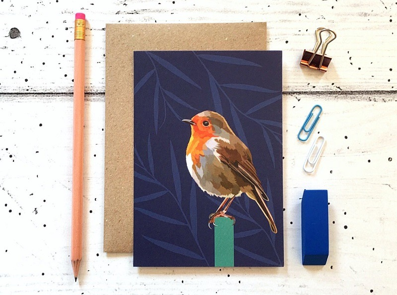 robin card against a cream background with pencil eraser and paper clips