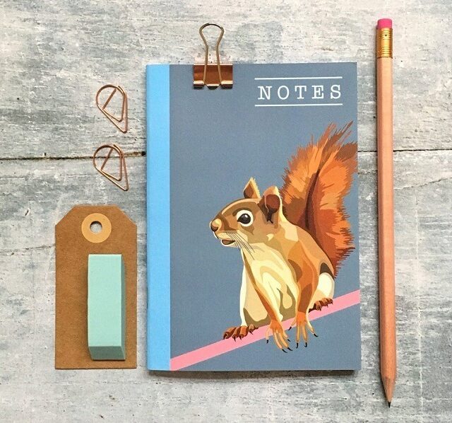 squirrel notebook against grey background with pencil and luggage tag
