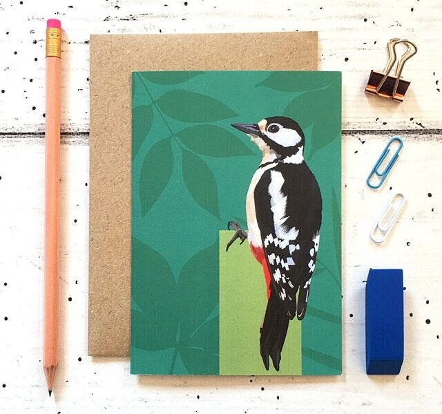 woodpecker card against a cream background with pencil rubber and paper clip