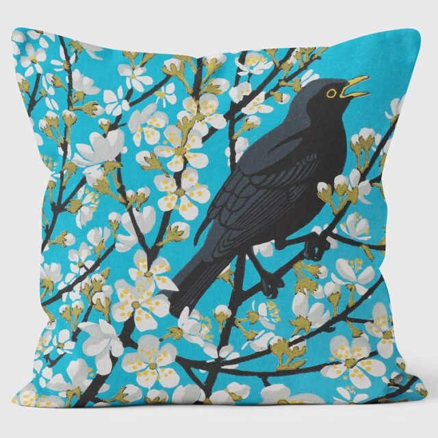 blackthorn blackbird cushion shows blackbird in blackthorn bush against turquoise background