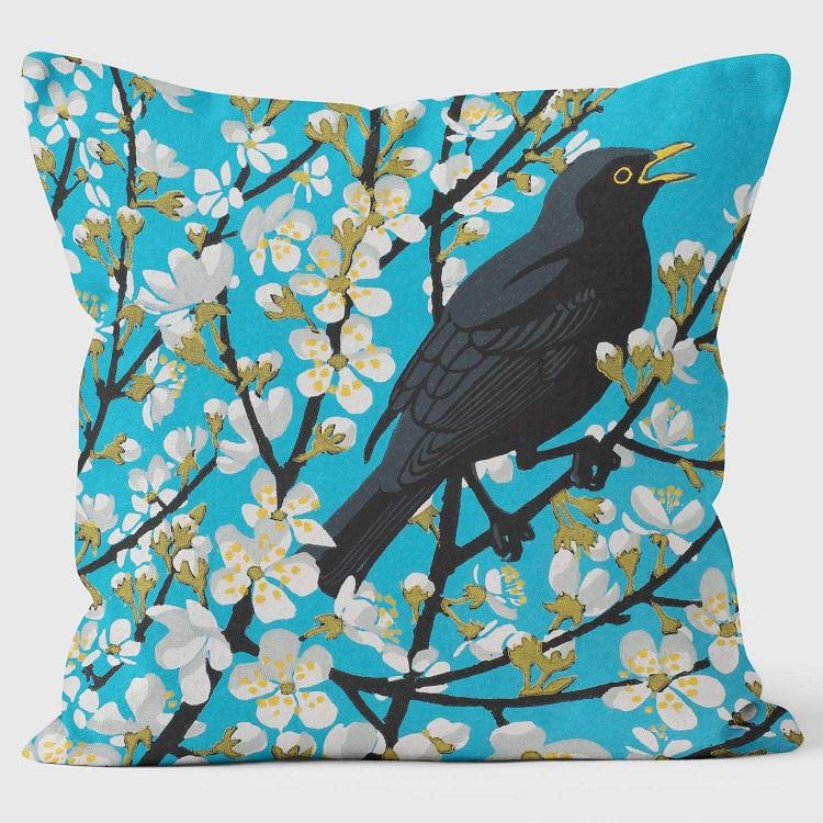 blackthorn blackbird cushion shows blackbird in blackthorn bush against turquoise background