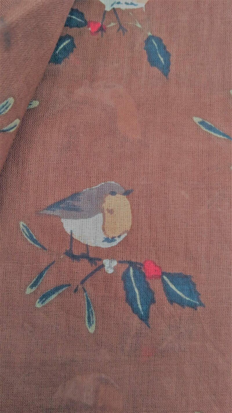 detail of robins on holly leaves against a brown fabric background