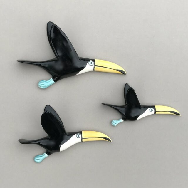 flying toucan trio of three ceramic birds facing right on a grey wall