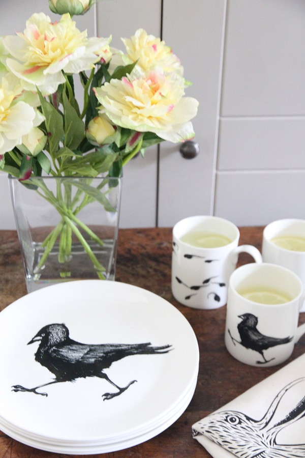 jackdaw plate in foreground with jackdaw mug and vase of flowers behind