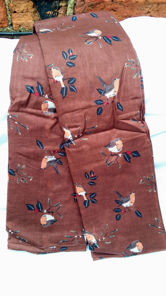 browny purple scarf with robins on it lying on a white background