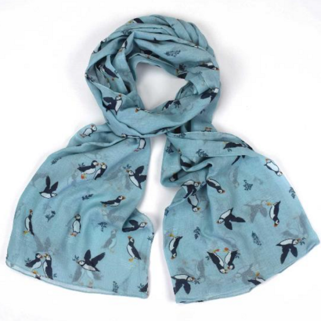 floral scarf with puffins on a blue background tied loosely in a knot