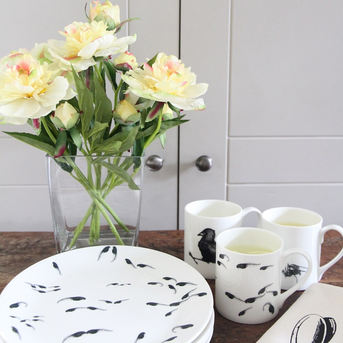 tadpoles plate in foreground with tadpoles mug and vase of flowers behind