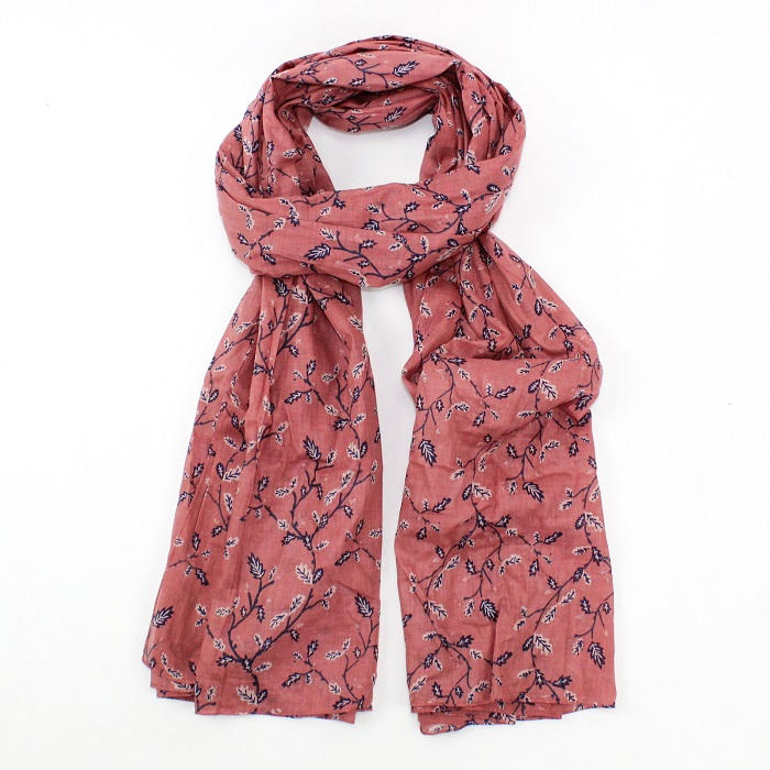 scarf with dusky pink background and oak leaves in navy and white tied loosely in a knot