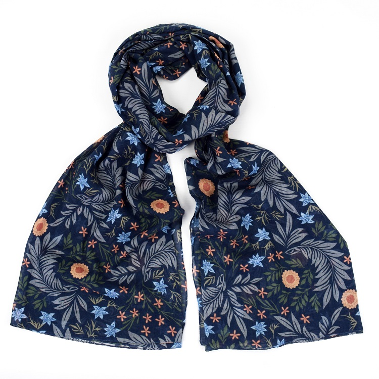 floral scarf with dark blue background and small flowers tied loosely in a knot