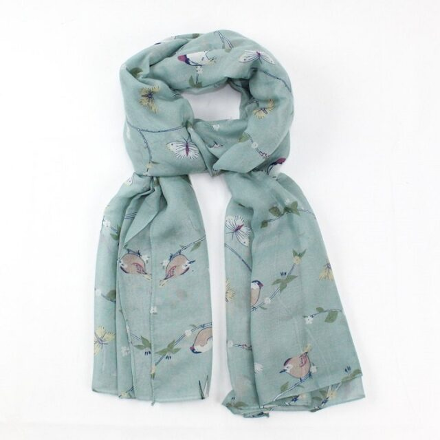 scarf with light blue background and woodpeckers on branches tied loosely in a knot