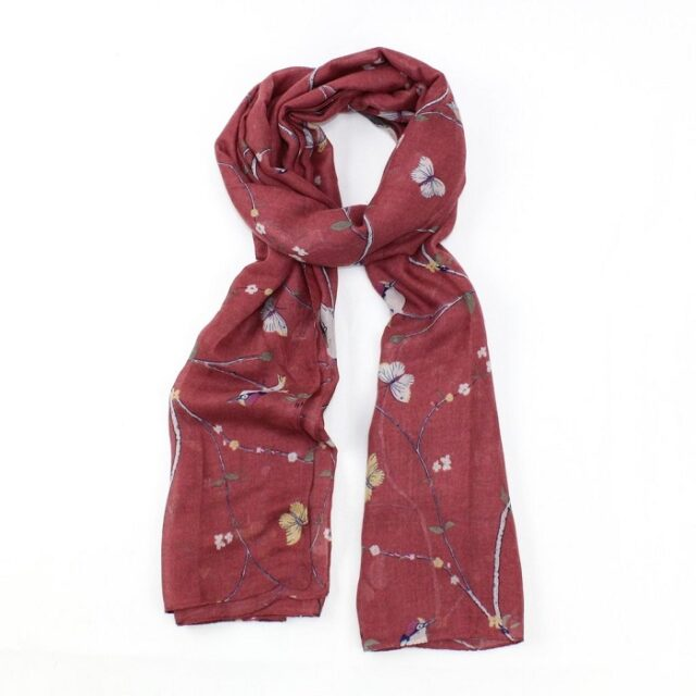 scarf with red background and woodpeckers on branches tied loosely in a knot