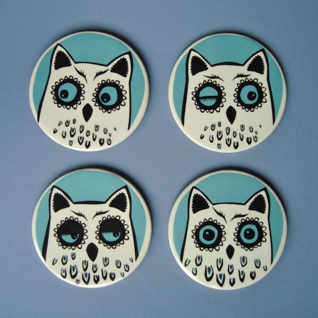 Four turquoise and white ceramic owl coasters against a blue background