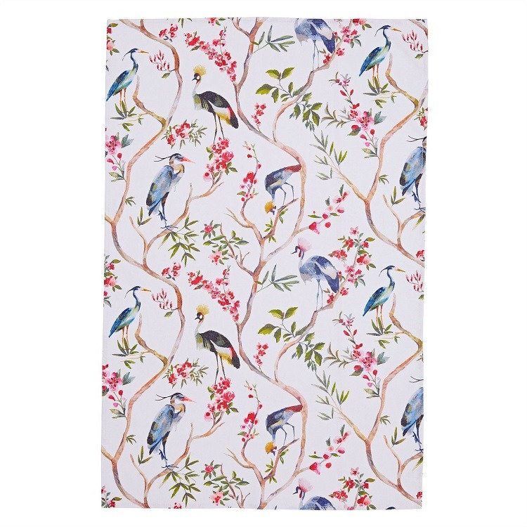 oriental birds tea towel shows blue and black birds against white background with delicate tree stems and pink blooms